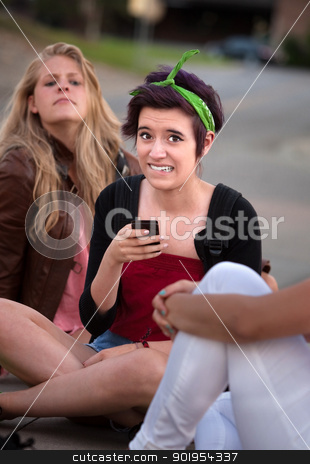 Embarassed Girl with Phone stock photo, Embarrassed teenage girl holding phone outside with friends by Scott Griessel