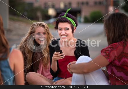 Excited Female Teens Looking at Phone stock photo, Excited teenage girls looking at a phone outside by Scott Griessel