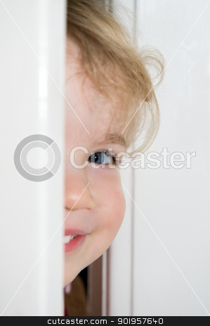 Smiling little girl stock photo, Smiling young girl behind a door. Focus is on the eye by Picturehunter