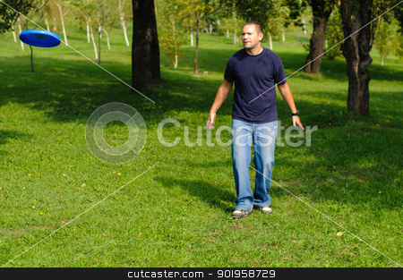 Young man playing frisbee stock photo, Young man playing frisbee on green grass by nvelichko