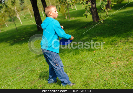Little boy playing frisbee stock photo, Little boy playing frisbee on green grass by nvelichko
