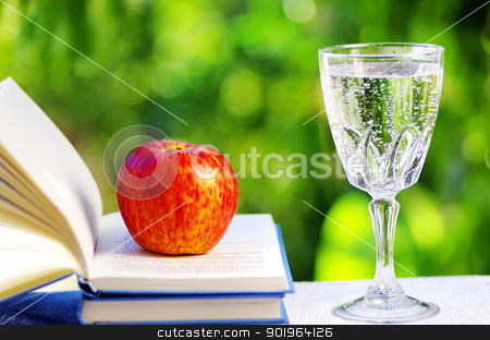 Apple on open book and water cup stock photo, Apple on open book and water cup by Inacio Pires