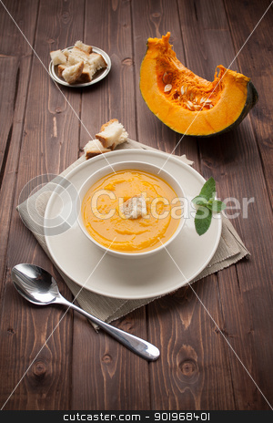 Vellutata di zucca - pumpkin soup stock photo, Bowl of pumpkin soup with bread crouton on white wood table by Giordano Aita