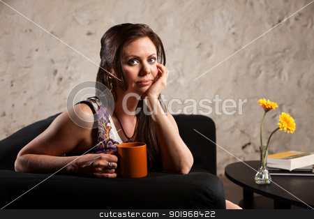 Serious Woman Sitting with Mug stock photo, Serious Caucasian brunette female sitting indoors and holding mug by Scott Griessel