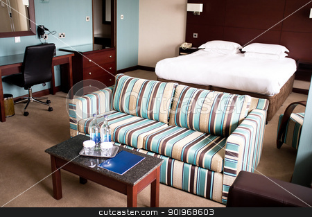 Suite room of a hotel stock photo, Suite room of a hotel with a sofa neatly placed in the middle and mini table placed by Ishay Botbol