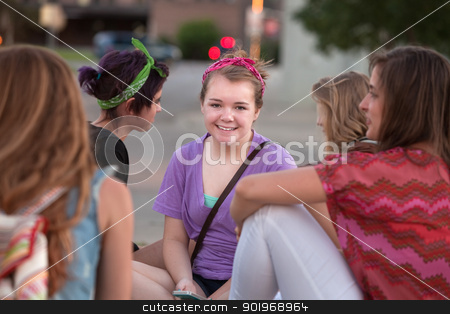 Cute Teen in Purple with Friends stock photo, Cute smiling female student in purple sitting among friends by Scott Griessel