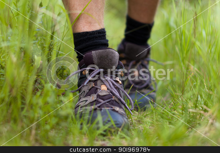 Hicking shoes in outdoor action stock photo, Closeup of hiking shoes in a grass by Kamila Starzycka