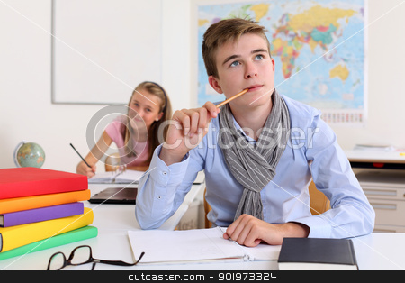 Student thinking in classroom stock photo, Photo of a handsome young male student thinking in class with a female student in the background. by © Ron Sumners