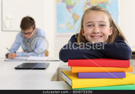 Happy student in her classroom stock photo, Photo of a pretty young girl smiling in her classroom with a male in the background writing and reading. by © Ron Sumners