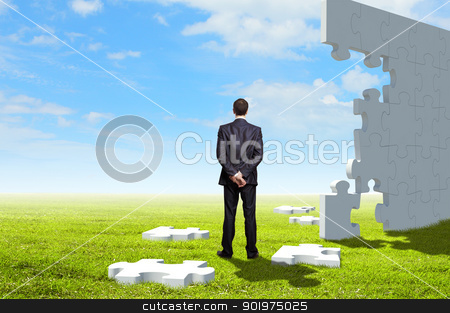 Businessman with a puzzle pieces stock photo, Businessman with a puzzle pieces on the background by Sergey Nivens