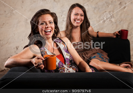 Pair of Laughing Women with Cups stock photo, Two pretty young women laughing and holding cups by Scott Griessel