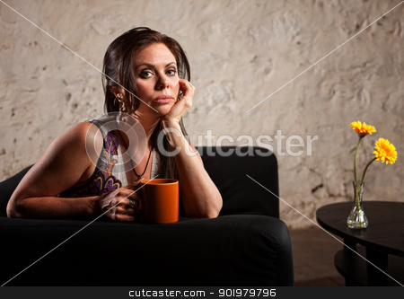 Serious Lady on Sofa stock photo, Serious young woman holding coffee mug sitting near table by Scott Griessel