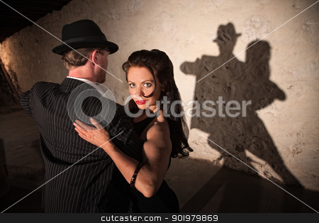 Dancing Couple In A Loving Embrace stock photo, Two tango dancers performing under spotlight indoors by Scott Griessel