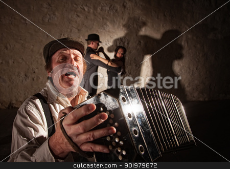 Accordion Player Singing For Dancers stock photo, Handsome singer playing accordion with tango dancers in background by Scott Griessel