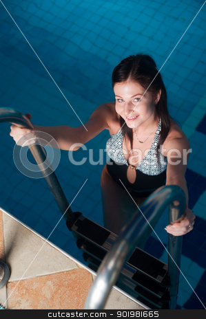 Attractive girl in swimming pool stock photo, Young beautiful woman sitting on stairs of the swimming pool by Aikon