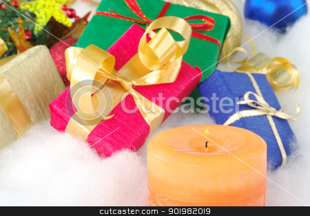 Christmas Presents stock photo, Lit orange candle and colorful presents with Christmas decoration on cotton (Selective Focus, Focus on candle) by Ildi Papp
