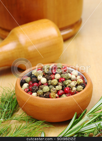 Pepper Corns stock photo, Black, white, green and red pepper corns in a ceramic bowl with other herbs (rosemary, dill) in the foreground and a mortar and pestle in the background (Selective Focus, Focus on the front of the bowl and the pepper corns)  by Ildi Papp