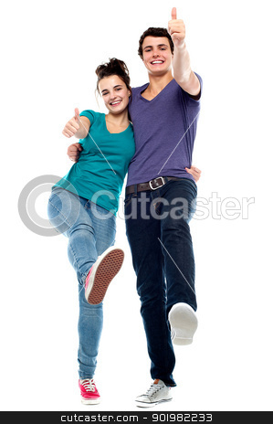 Teen love couple enjoying themselves, gesturing thumbs up stock photo, Teen love couple enjoying themselves, gesturing thumbs up. All against white background by Ishay Botbol