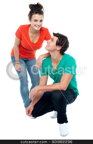 Adorable teenage love couple posing together stock photo, Adorable young guy squatting on floor and looking at his girlfriend by Ishay Botbol