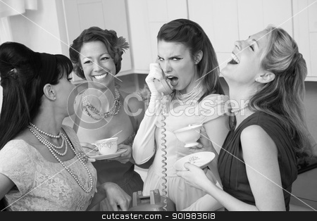 Woman Laughing at Friend on Phone stock photo, Outraged woman on phone with three friends in a kitchen by Scott Griessel