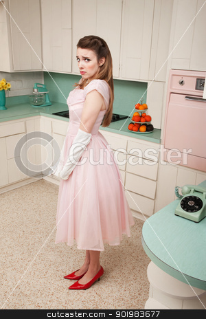 Unhappy Lady stock photo, Unhappy young Caucasian woman stands alone by a phone in a retro-style kitchen by Scott Griessel