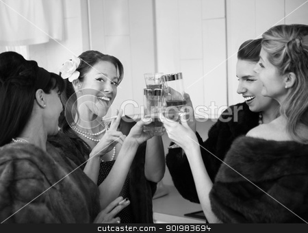 Women Raising A Toast  stock photo, Group of four women with fur coats raising a toast in a kitchen by Scott Griessel