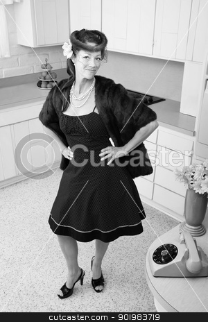 Smiling Woman In a Mink Coat stock photo, Smiling Caucasian woman in mink coat and hands on hip in a retro kitchen scene by Scott Griessel