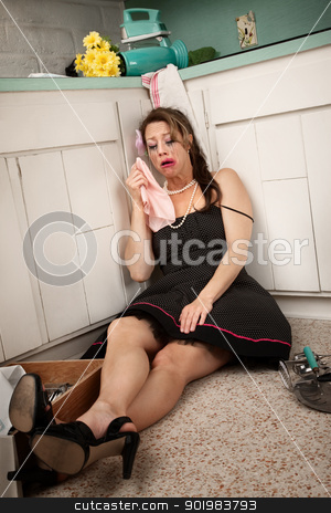 Drunk Woman Crying stock photo, Drunk woman on kitchen floor crying and holding napkin by Scott Griessel