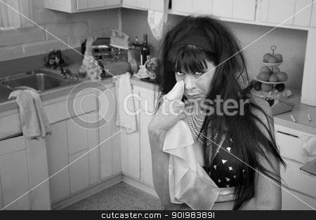 Weeping Woman stock photo, Weeping woman in a kitchen wipes tears using napkin by Scott Griessel