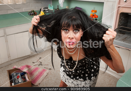 Woman Pulls Her Hair stock photo, Desperate housewife in a kitchen pulls her hair by Scott Griessel