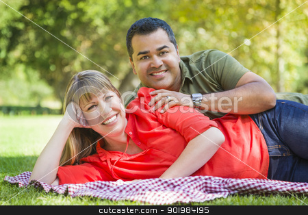 Attractive Mixed Race Couple Portrait at the Park stock photo, Happy Attractive Mixed Race Couple Portrait on a Blanket at the Park. by Andy Dean