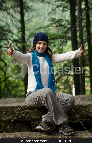 Happy woman stock photo, Beautiful and happy young woman sitting on a stonewall with thumb up  by ikostudio