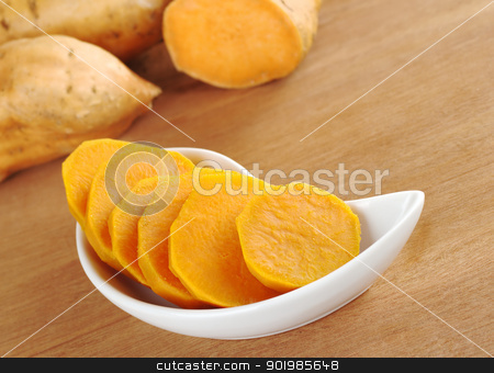 Cooked Sweet Potato Slices stock photo, Cooked sweet potato (lat. Ipomoea batatas) cut in slices in white bowl on wooden surface with sweet potatoes in the background (Selective Focus, Focus on the sweet potato in the bowl)  by Ildi Papp