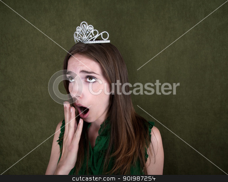 Bored Homecoming Queen stock photo, Young woman with crown on green background yawns by Scott Griessel