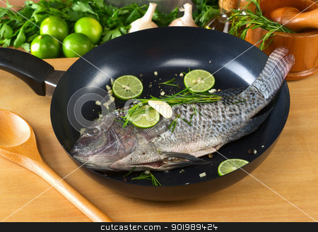 Fish Called Tilapia in Pan stock photo, Raw tilapia with condiments (pepper corns, lime slices, garlic and rosemary) in frying pan with a wooden stirring spoon (Selective Focus, Focus on the head and belly of the fish) by Ildi Papp
