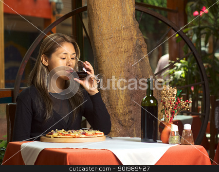 Latina Drinking Wine in Restaurant stock photo, Beautiful young Peruvian woman enjoying her wine and eating pizza in a restaurant  by Ildi Papp