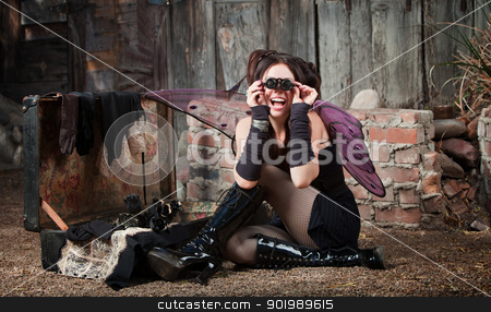 Excited Fairy  stock photo, Excited fairy sitting on ground looks through loupe glasses by Scott Griessel