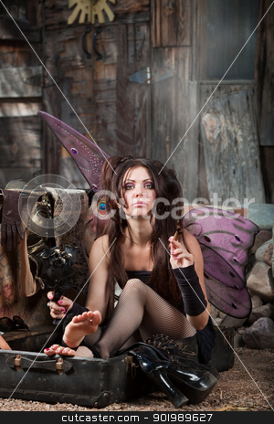 Smoking Fairy in Suitcase stock photo, Beautiful fairy sitting in suitcase holds black roses and smokes cigar by Scott Griessel