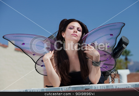 Fairy On Rooftop stock photo, Pretty Caucasian fairy pouts and sits on rooftop by Scott Griessel