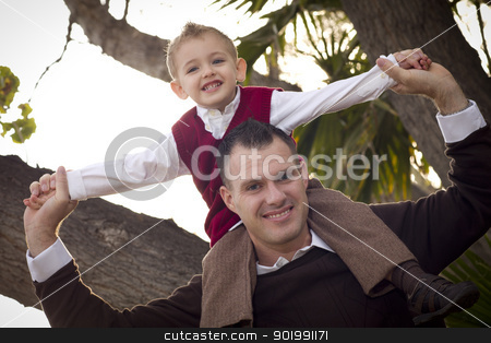 Handsome Father and Son in the Park stock photo, Young Laughing Father and Child Having Piggy Back Fun in the Park. by Andy Dean