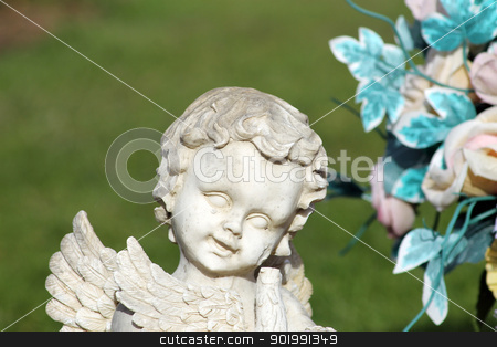 Angel statue and flower bouquet stock photo, Happy angel statue and flower bouquet, part of a cemetery memerial with green grass background and copy space. by Martin Crowdy