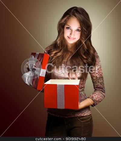 Beautiful brunette peeking inside gift box. stock photo, Portrait of a beautiful young brunette peeking inside shiny red gift box in creative lighting. by exvivo