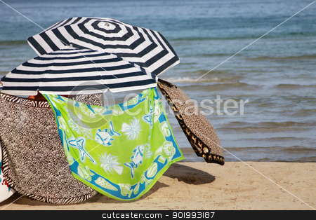 Parasols on sandy beach stock photo, Parasols keeping sunbathers on shade, sandy beach with sea in background. by Martin Crowdy