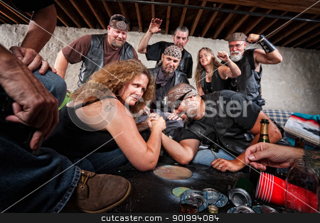 Grinning Woman Wins Arm Wrestling Match stock photo, Tough grinning woman defeats biker in arm wrestling contest by Scott Griessel