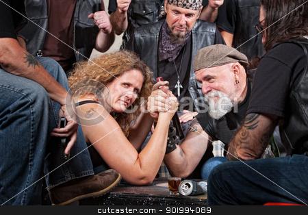 Serious Woman Arm Wrestling stock photo, Serious woman in arm wrestling contest with biker gang by Scott Griessel