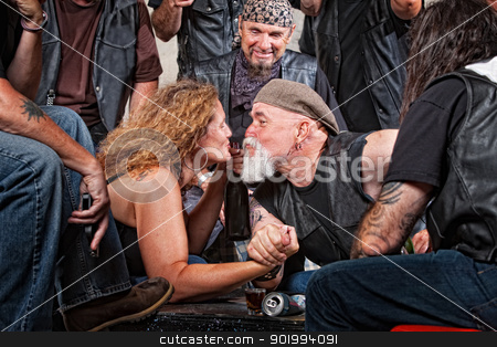 Lovers Kiss While Arm Wrestling stock photo, Two biker gang lovers kiss while arm wrestling by Scott Griessel