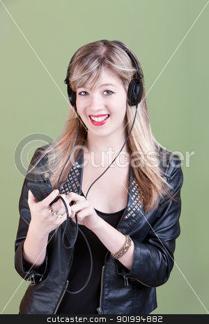 Teenaged Girl with Handheld Phone or Audio Device stock photo, Retro-styled young Caucasian woman listens to music on headphones over green background by Scott Griessel