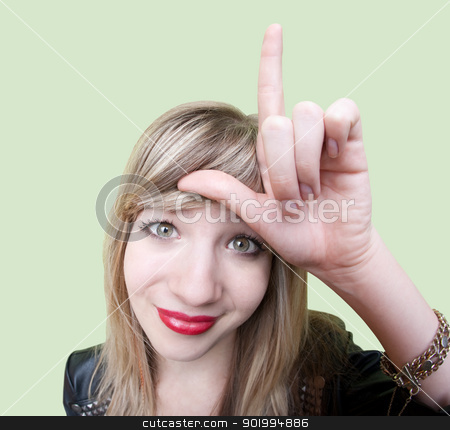 Lady Makes Loser Sign stock photo, Cute young Caucasian woman makes loser sign on her forehead over green background by Scott Griessel