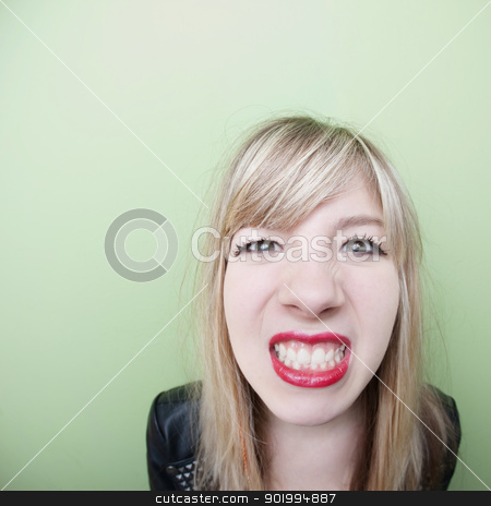 Girl Clenches Teeth stock photo, Young Caucasian lady clenches her teeth over green background by Scott Griessel