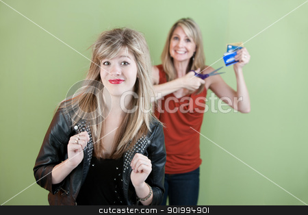 Mom Gestures To Destroy Credit Card stock photo, Happy mom gestures to destroy daughter's credit cards over green background by Scott Griessel